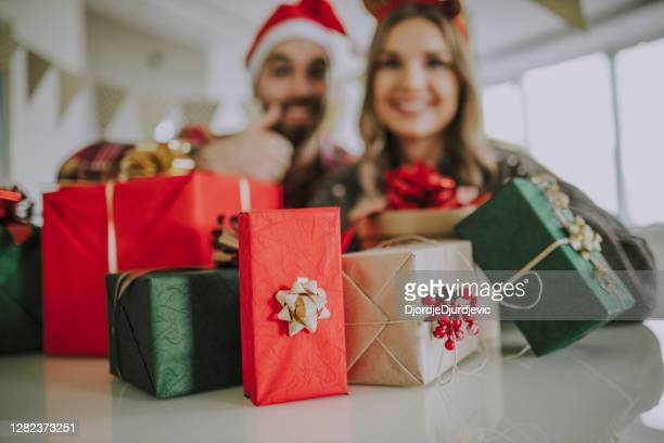 young couple celebrating new year and packing new years present at home - 25 29 years stock pictures, royalty-free photos & images