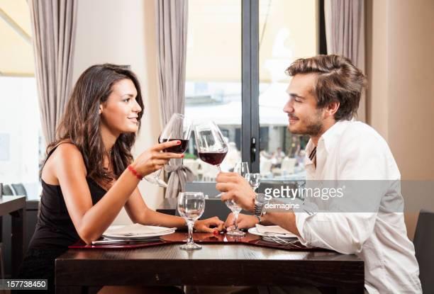 jovem casal celebrando com vinho tinto no restaurante - bem vestido - fotografias e filmes do acervo