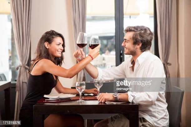 Jovem Casal Celebrando com vinho tinto no restaurante
