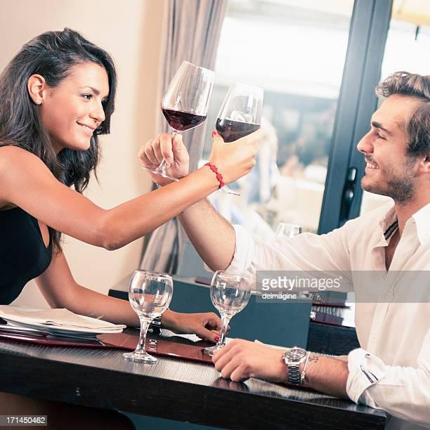 Jeune couple célébrer avec vin rouge au restaurant