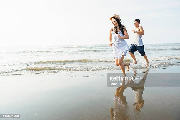 Young couple chasing each other on the beach.