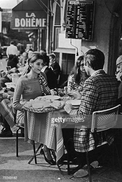 A young couple chat over wine and cheese at a Paris cafe circa 1960