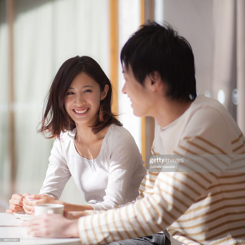 Young couple chatting at an open cafe : Stock Photo