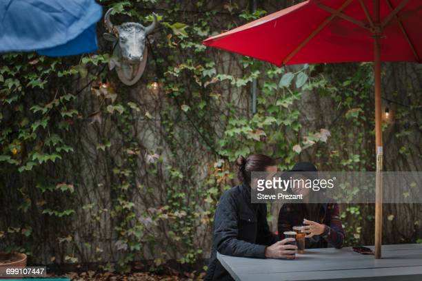 'Young couple chatting in beer garden in evening, Brooklyn, New York, USA'