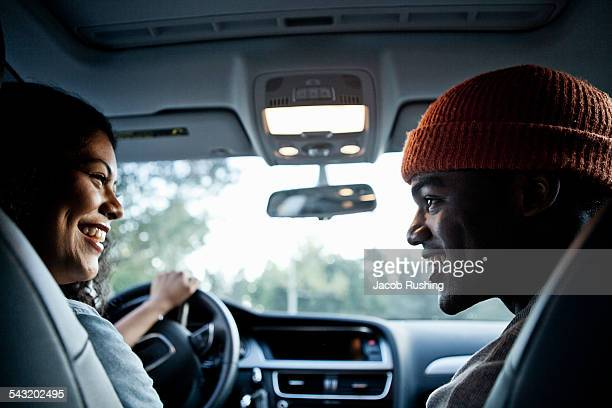 Young couple chatting in front seat of car
