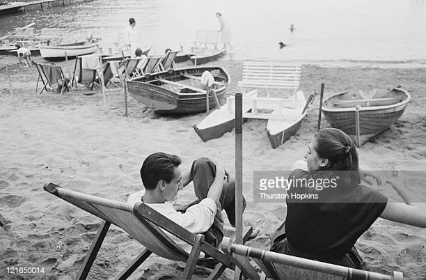 A young couple chatting on Paraggi Beach near the tourist resort of Portofino Italy August 1952 Original Publication Picture Post 6023 unpub