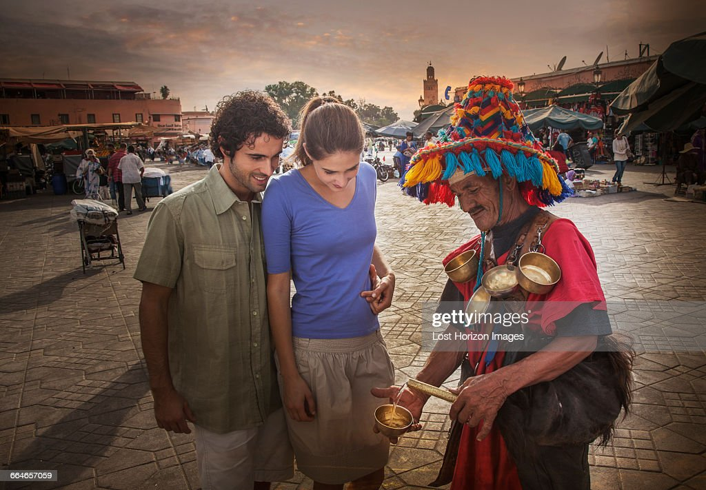 Young couple chatting with market trader, Jemaa el-Fnaa Square, Marrakesh, Morocco : Stock Photo