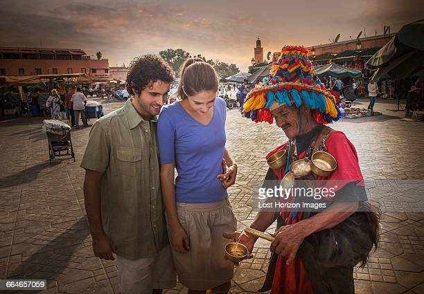 Young couple chatting with market trader, Jemaa el-Fnaa Square, Marrakesh, Morocco