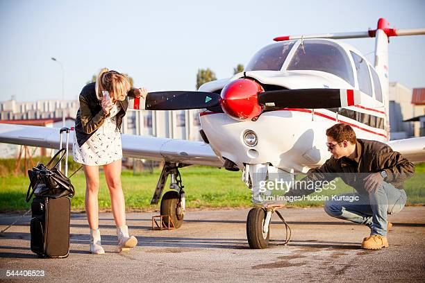 Young couple checking propeller airplane