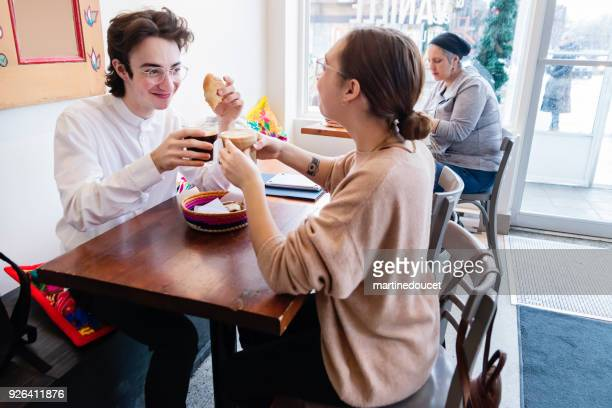 """young couple cheering with coffee in a local coffee shop. - """"martine doucet"""" or martinedoucet stock pictures, royalty-free photos & images"""