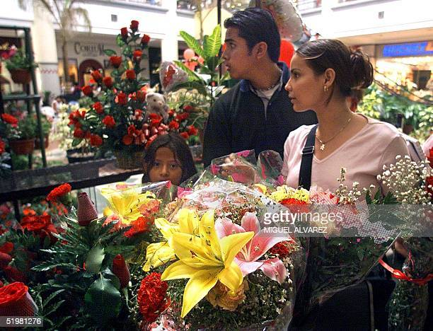 A young couple choose flowers as a Saint Valentine's gift 14 February 2001 in a Flower Fair in a shopping center of Managua Nicaragua Una pareja de...