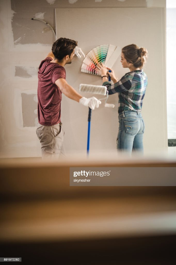Young couple choosing the right color for their wall in new apartment. : Stock Photo
