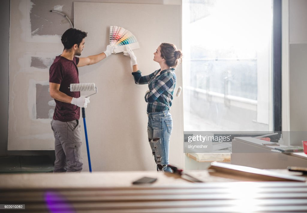 Young couple choosing the right color for their wall while renovating apartment. : Stock Photo