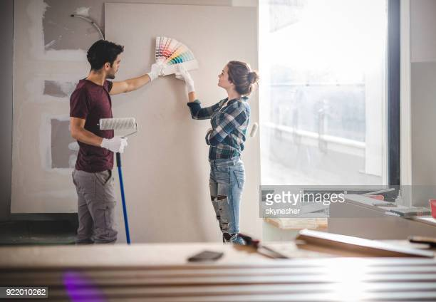 young couple choosing the right color for their wall while renovating apartment. - at home imagens e fotografias de stock
