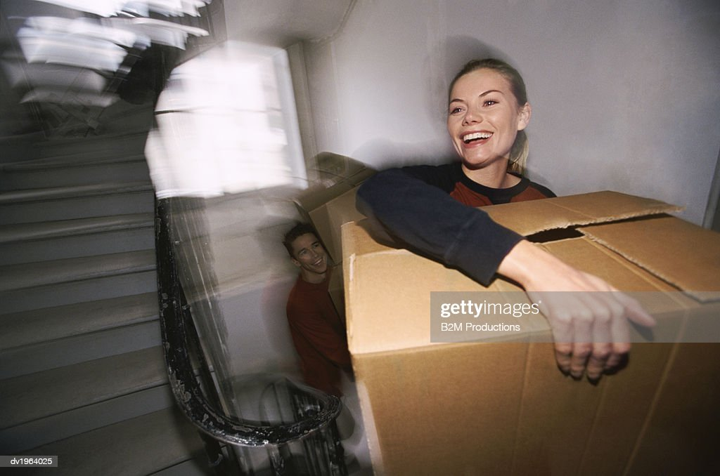 Young Couple Climb up a Stairway Carrying Cardboard Boxes : Stock Photo