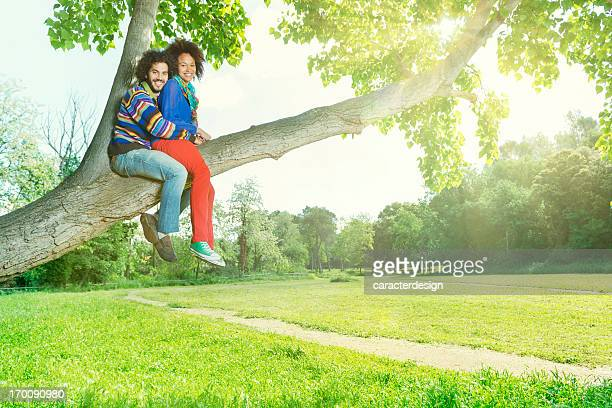 Young couple climbing a tree