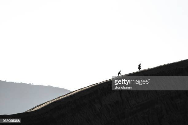 a young couple climbing mt. bromo in morning mist. mt. bromo is one of the most visited tourist attractions in east java, indonesia. - shaifulzamri stock pictures, royalty-free photos & images