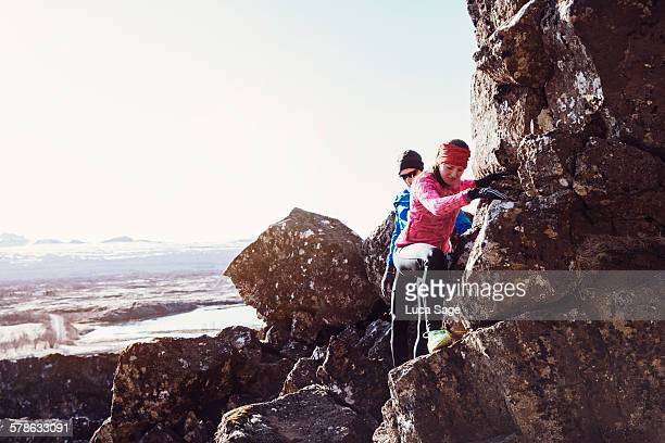 Young couple climbing over rocks in Iceland