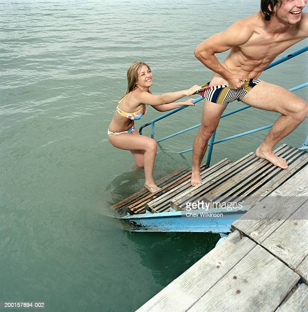 Young couple climbing up jetty steps, woman pulling down man?s shorts