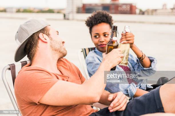 Young couple clinking beer bottles on rooftop