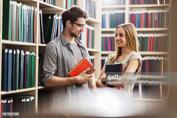 Young couple communicating in a library.