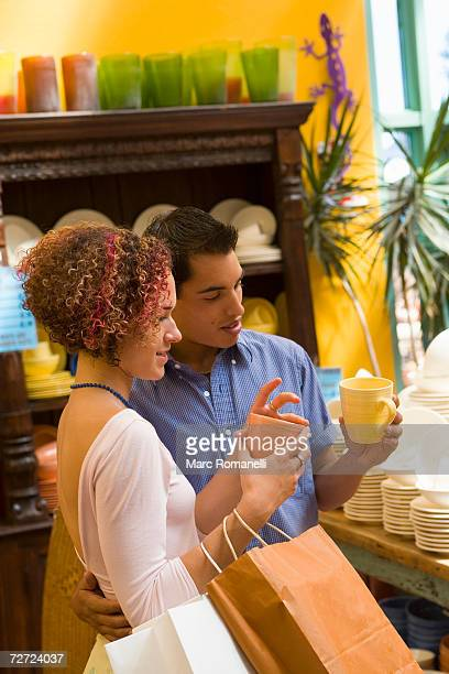 young couple comparing ceramic mugs in shop - ceramic stock pictures, royalty-free photos & images