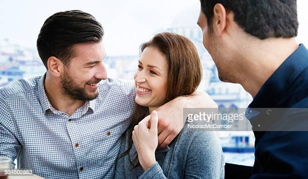 Young couple connect on Istanbul cruise in front of friend