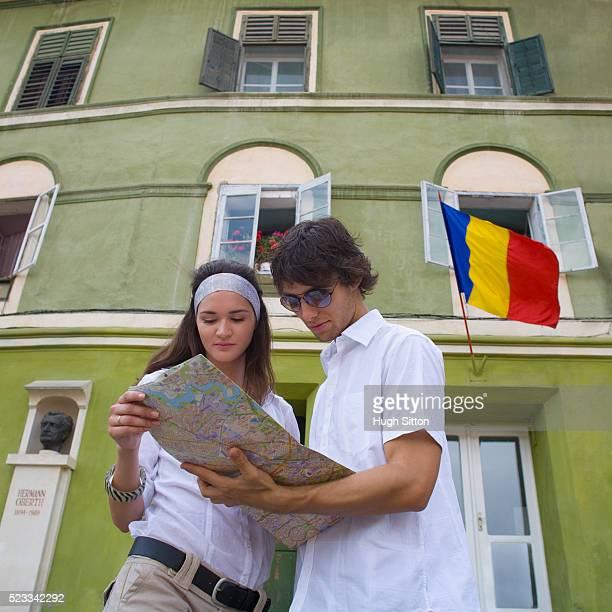 young couple consulting a map - hugh sitton bildbanksfoton och bilder