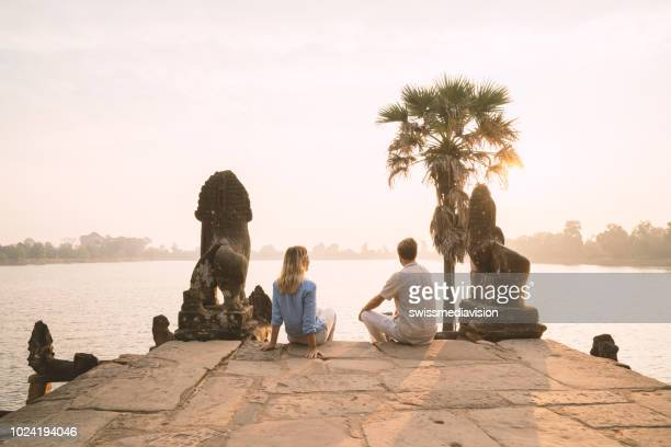young couple contemplating ancient temple by the lake in cambodia , sunrise, people travel discovery couple romance concept - cambodia stock pictures, royalty-free photos & images