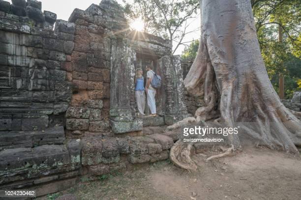 jovem casal contemplando o antigo templo no camboja, angkor wat siem reap ásia - templo - fotografias e filmes do acervo