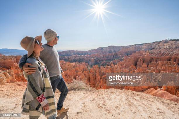 young couple contemplating nature enjoying travel and adventure - america - national park stock pictures, royalty-free photos & images