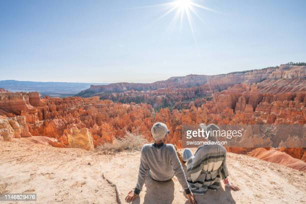 young couple contemplating nature enjoying travel and adventure - america - bryce canyon stock pictures, royalty-free photos & images