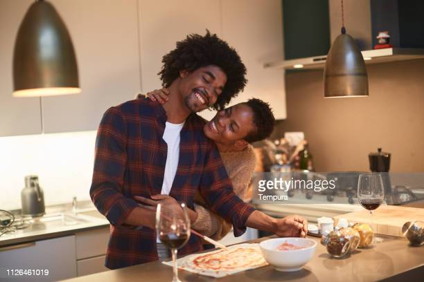 young couple cooking at home and celebrating saint valentine - valentines day dinner stock pictures, royalty-free photos & images