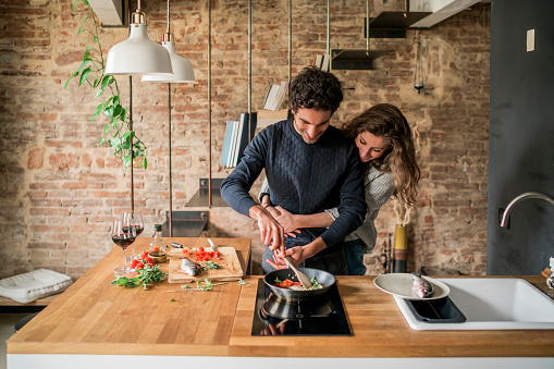 Young couple cooking fish cuisine at kitchen counter hob - gettyimageskorea