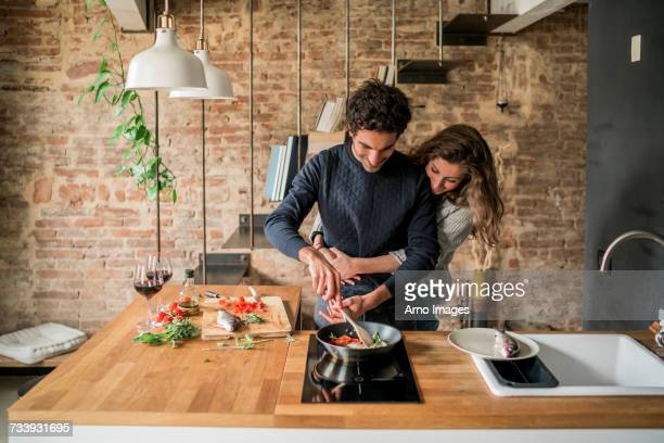 young couple cooking fish cuisine at kitchen counter hob - couples stock pictures, royalty-free photos & images