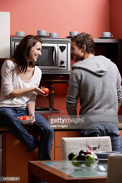 young couple cooking in kitchen smiling at each other