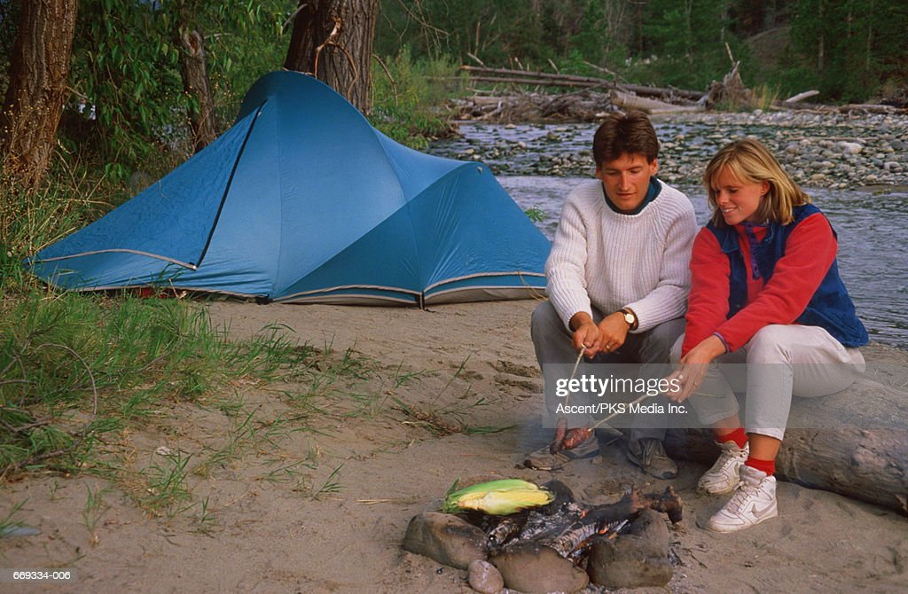 Young couple cooking on c& fire blue tent pitched by river  Stock Photo  sc 1 st  Getty Images & Young Couple Cooking On Camp Fire Blue Tent Pitched By River Stock ...