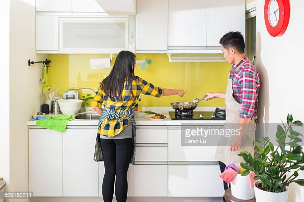 Young couple cooking together in kitchen.
