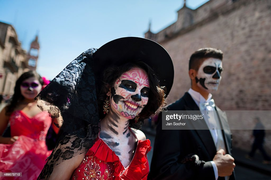 A young couple, costumed as 'La Catrina', a Mexican pop culture icon representing the Death, walks through the town during the Day of the Dead festivities on November 01, 2014 in Morelia, Mexico. Day of the Dead is a syncretic religious holiday, celebrated throughout Mexico, combining the death veneration rituals of the ancient Aztec culture with the Catholic practice. Based on the belief that the souls of the departed may come back to this world on that day, people gather on the gravesites praying, drinking and playing music, to joyfully remember friends or family members who have died and to support their souls on the spiritual journey.