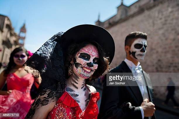 A young couple costumed as 'La Catrina' a Mexican pop culture icon representing the Death walks through the town during the Day of the Dead...