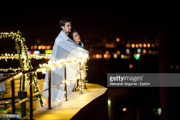 Young Couple Covered With Blanket Standing On Illuminated Terrace At Night