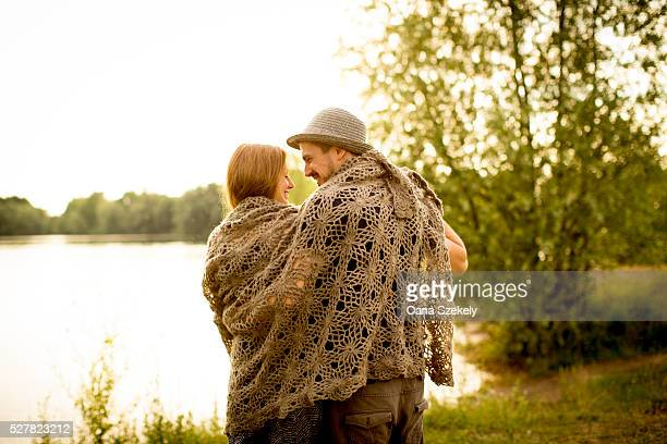 Young couple covered with shawl walking at lakeshore