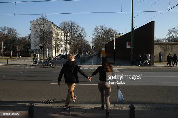 A young couple cross the street near the Berlin Wall memorial at Bernauer Strasse on February 25 2014 in Berlin Germany In the black and white photo...