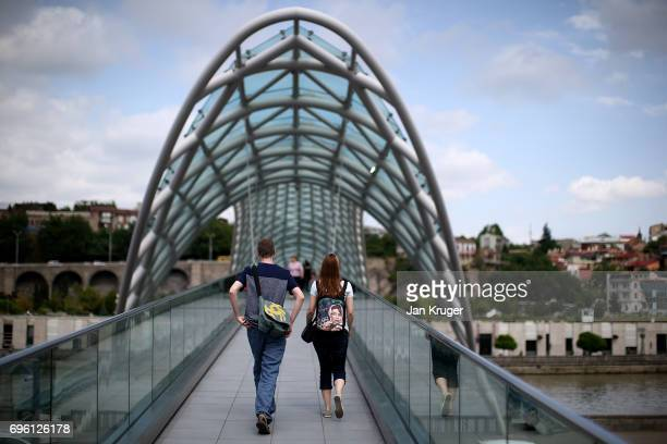 A young couple crosses The Bridge Of Peace on June 14 2017 in Tbilisi Georgia The 2017 World Rugby Under 20 Championship are taking place in June in...
