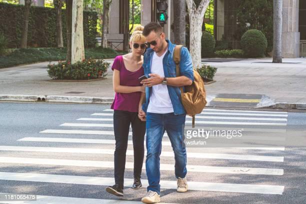pares novos que cruzam uma rua na crosswalk usando um telefone esperto. - pedestre - fotografias e filmes do acervo