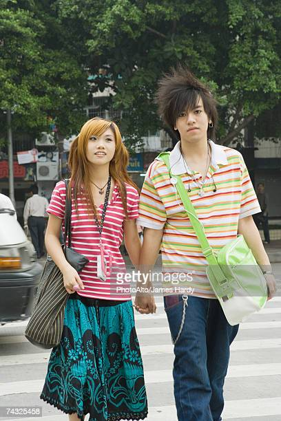 young couple crossing street, holding hands, three quarter length - three quarter length ストックフォトと画像