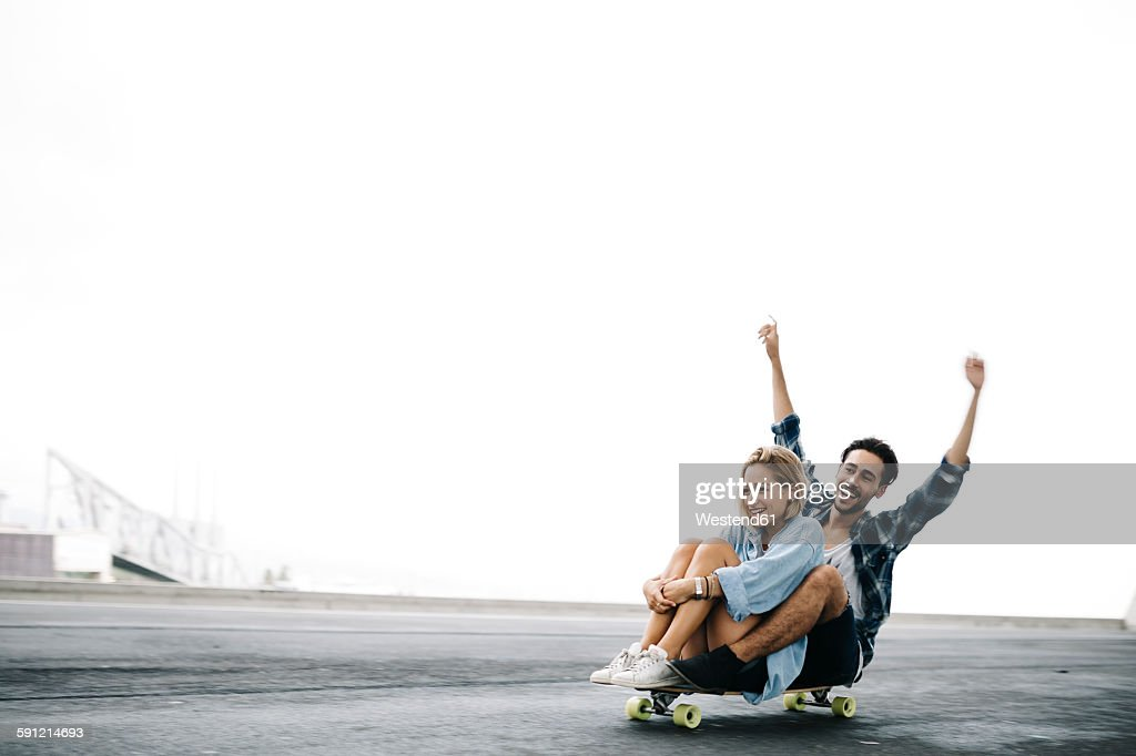 Young couple cruising on a longboard : Stock Photo