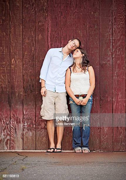 A young couple cuddles against the wall of a barn.