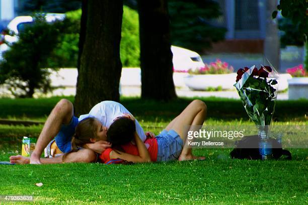Young couple cuddles in a park, close to a bouquet of roses.