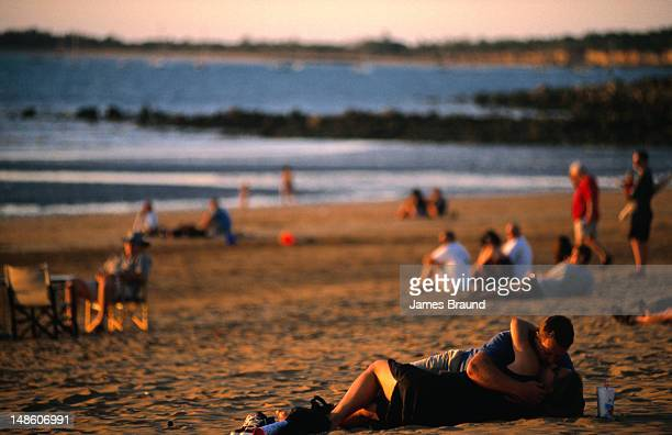 Young couple cuddling at sunset, Mindil Beach.